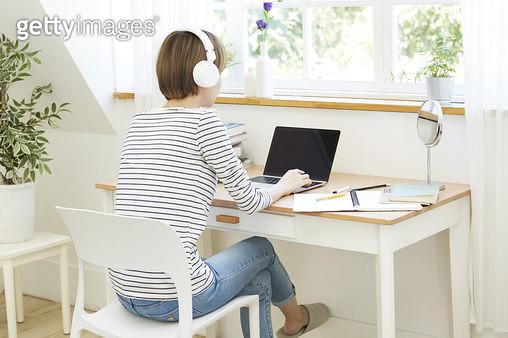 의자에 앉아 헤드폰을 끼고 노트북으로 하는 젊은여자 - gettyimageskorea