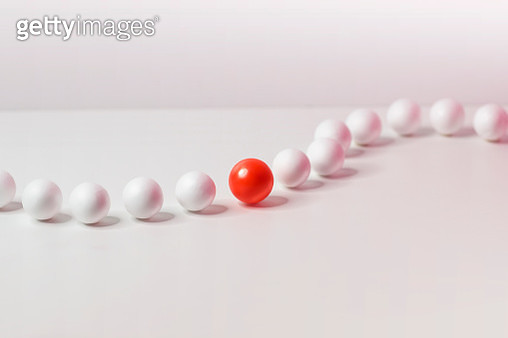 One red sphere looking outstanding from a row of moving white sphere on white background. - gettyimageskorea