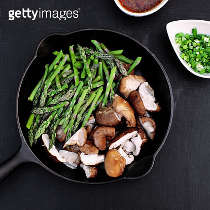 Cut asparagus and shiitake mushrooms in a cast iron skillet with green onions and chili sauce on the side on a black background. - gettyimageskorea