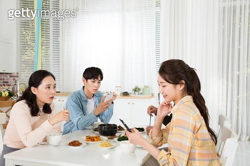 식사하며 스마트폰을 하는 딸, 가족 식사시간 소통단절 - gettyimageskorea