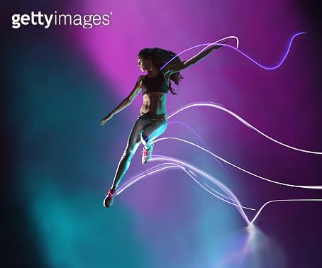 Female athlete jumping, leaving streaks of light - gettyimageskorea