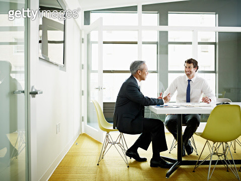 Coworkers discussing project in conference room - gettyimageskorea