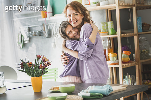 Mom and daughter hugging in the kitchen - gettyimageskorea