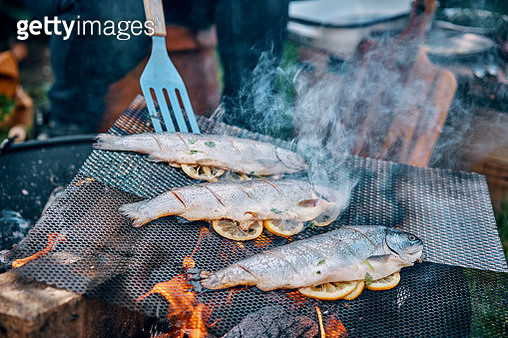 Preparing Fish for Cooking Over Open Campfire - gettyimageskorea
