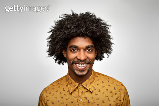 Close-up portrait of young businessman smiling. Confident male professional is having curly hair. He is wearing smart casuals against white background. - gettyimageskorea