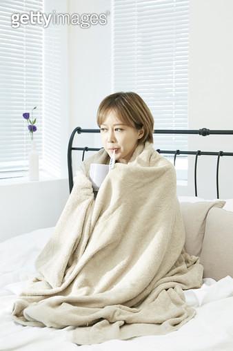 감기, 담요를 두르고 온도계를 입에 물고있는 젊은여자 - gettyimageskorea