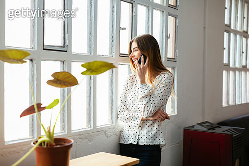 Happy young woman on cell phone at the window in office - gettyimageskorea