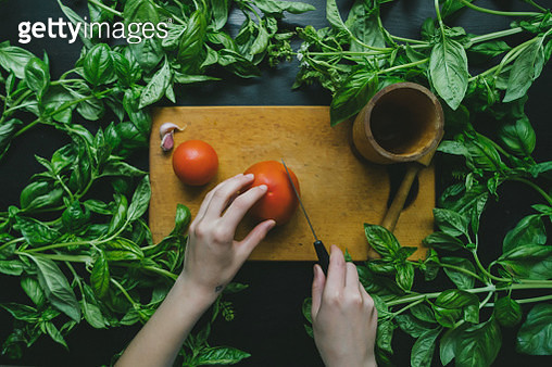 Tomato on cutting board among green leaves - gettyimageskorea