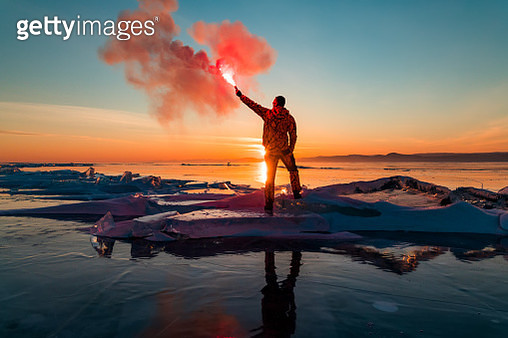 Man with hand flare at sunset on ice. Baikal in winter - gettyimageskorea