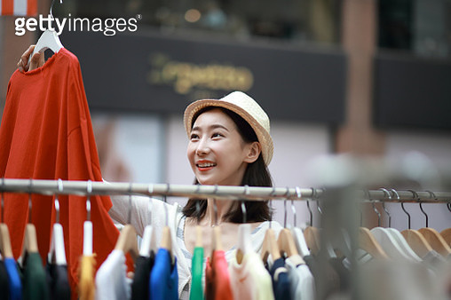 Young woman shopping clothes at outdoor market - gettyimageskorea