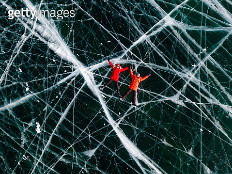 Couple - man and woman in the red jackets is lying on the transparent ice. Baikal, aerial view. Olkhon Island, Lake Baikal, Siberia, Russia - gettyimageskorea