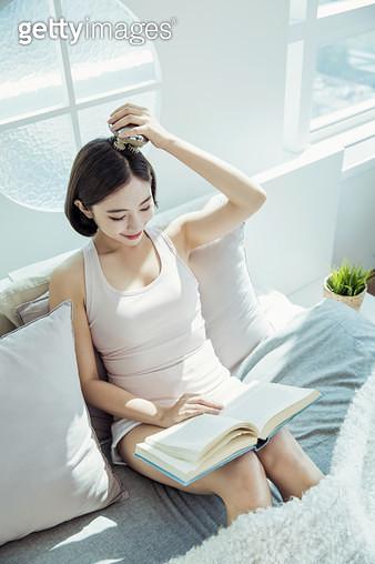 책을 읽으며 두피마사지를 하고 있는 여자 - gettyimageskorea