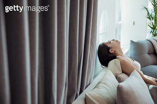 침대에 기대 우울해하는 여자 - gettyimageskorea