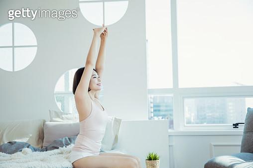 침대에 앉아 스트레칭을 하는 여자 - gettyimageskorea