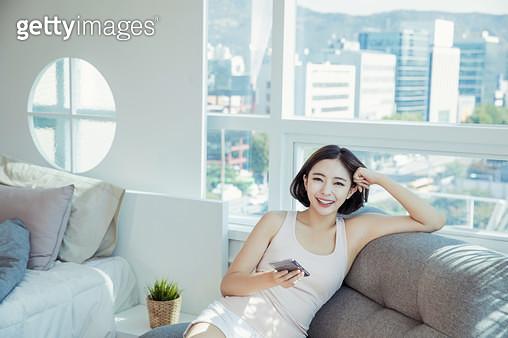 소파에 앉아 핸드폰을 하는 여자 - gettyimageskorea