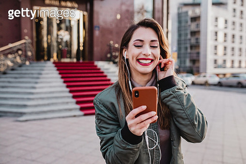 Photo of beautiful young woman in the city, listening music with headphones - gettyimageskorea