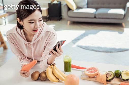 주방에서 핸드폰을 보는 여자 - gettyimageskorea