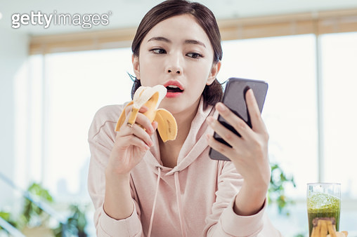 바나나를 먹으며 핸드폰을 보는 여자 - gettyimageskorea