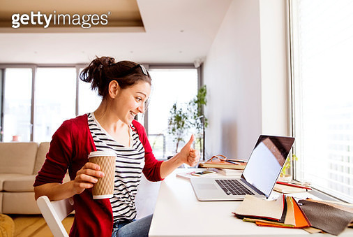 Smiling woman with coffee to go at desk at home - gettyimageskorea