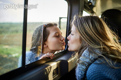 Mother and daughter kissing through the window of an off-road vehicle - gettyimageskorea