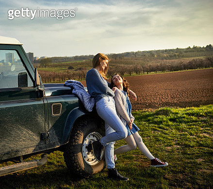Smiling mother with daughter on a field at an off-road vehicle - gettyimageskorea