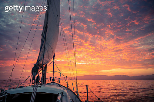 Sailboat Sailing In Sea Against Cloudy Sky During Sunset - gettyimageskorea