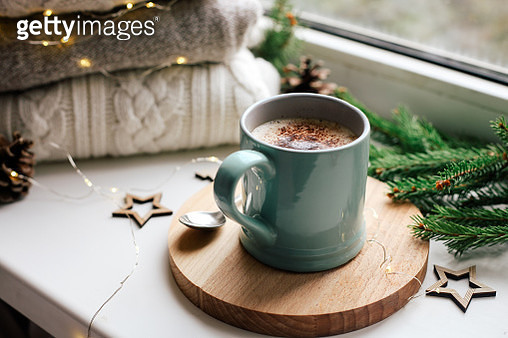 Cozy home picture of blue ceramic cup with coffee on window sill, Christmas decorations, warm knitted sweaters and pine tree green branches in background - gettyimageskorea
