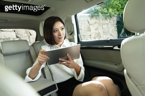 Young woman sitting in the car to see the tablet PC - gettyimageskorea