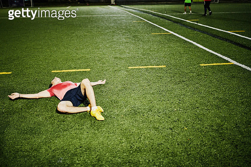 Exhausted male soccer player lying on field after evening soccer game - gettyimageskorea