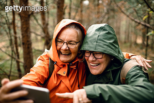 Close up of two female seniors taking a selfie while hiking in the forest - gettyimageskorea