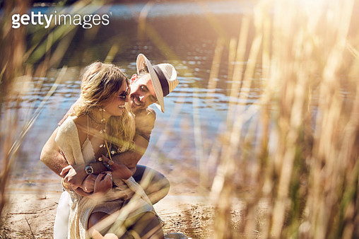 Affectionate young couple hugging at sunny summer riverside - gettyimageskorea
