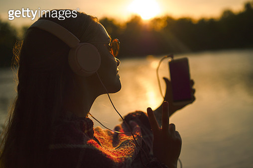 Young caucasian woman in white headphones takes a selfie while standing by the river at sunset. - gettyimageskorea