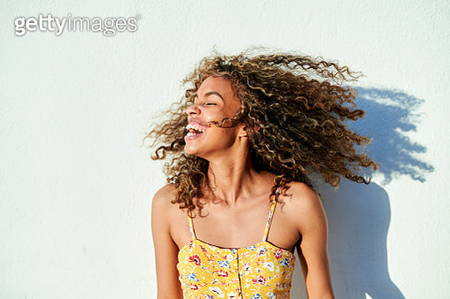 Portrait of woman moving her hair in front of white wall - gettyimageskorea