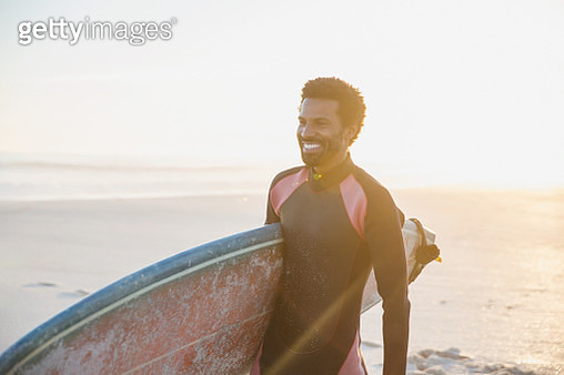Smiling male surfer walking with surfboard on sunny summer beach - gettyimageskorea