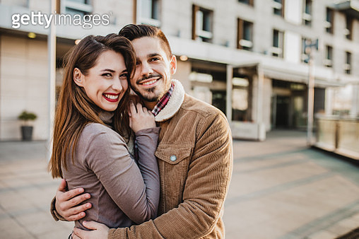 Portrait of young couple standing and hugging in the modern part of the city - gettyimageskorea