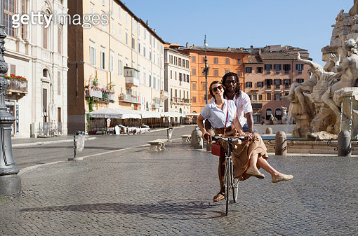 Beautiful biracial couple riding bicycle in deserted Piazza Navona, Rome, Italy - gettyimageskorea