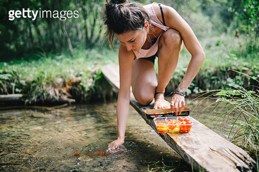 Young woman preparing vegetables for the picnic salad, washing tomatoes in the river stream. - gettyimageskorea