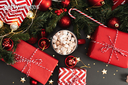 New Year and Christmas present on a black background and a wooden table. mug with cocoa and marshmallows with cinnamon and star anise - gettyimageskorea