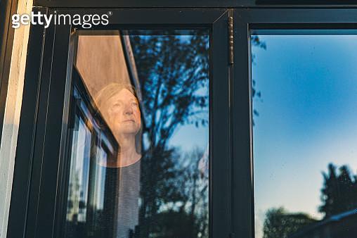 Senior woman looking through window - gettyimageskorea