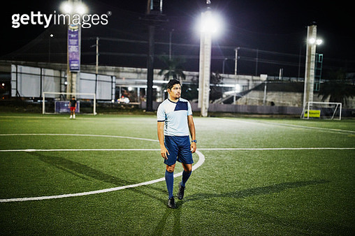 Portrait of male soccer player on field during evening game - gettyimageskorea
