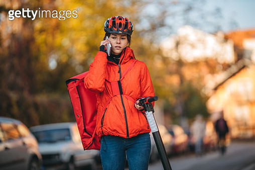 Food delivery girl on an electric scooter - gettyimageskorea