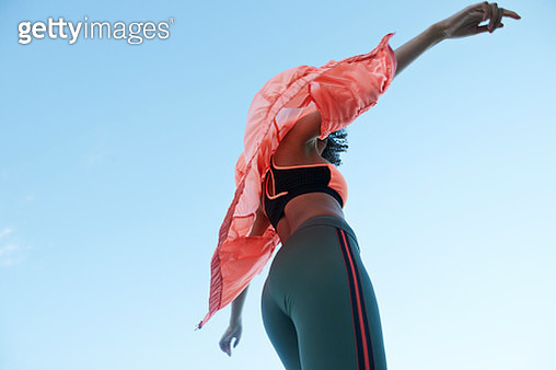 Fashionable female athlete wearing jacket with sports clothing against clear blue sky - gettyimageskorea