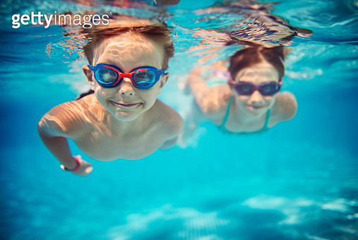 Smiling kids enjoying underwater swim in the pool towards the camera. Sunny summer day. Brother aged 5 is in the front, the sister is aged 9 and is swimming in the background. Slightly soft. - gettyimageskorea