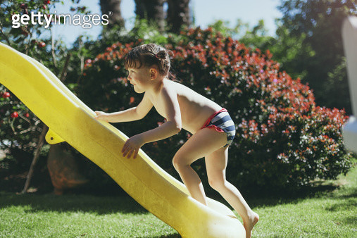 Girl in swimsuit climbing up a slide - gettyimageskorea