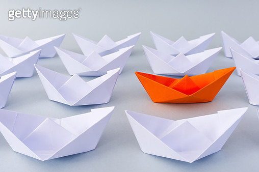 Orange colored paper boat leading a white paper boats. Business Leadership Concept. - gettyimageskorea