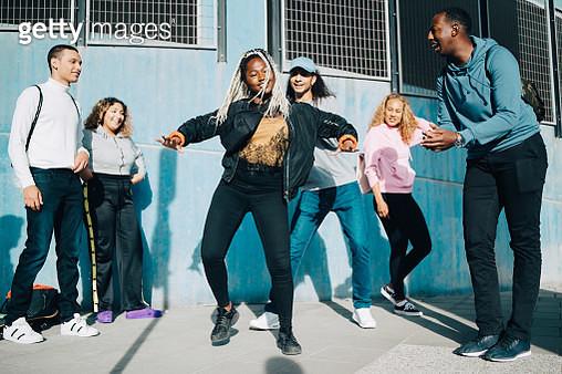 Smiling friends looking at teenage girl dancing on sidewalk in city - gettyimageskorea