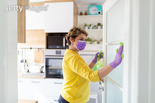 Middle aged woman disinfecting glass on the door - gettyimageskorea