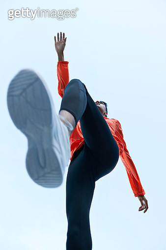 Sportsman with legs apart against clear sky - gettyimageskorea