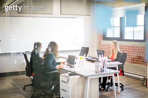 Three young businesswomen sitting at a desk and using a laptop. Office worker. Concentration, focus. Startup. Millennials. Women working together. - gettyimageskorea
