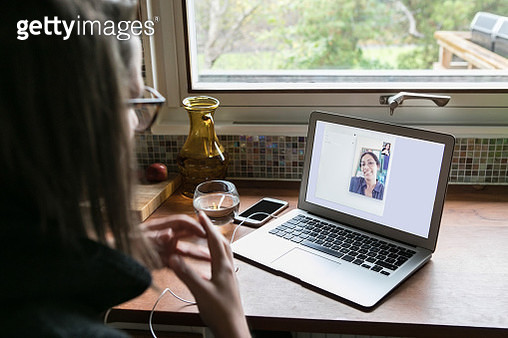 High angle view of businesswoman video calling female colleague on laptop in home office - gettyimageskorea